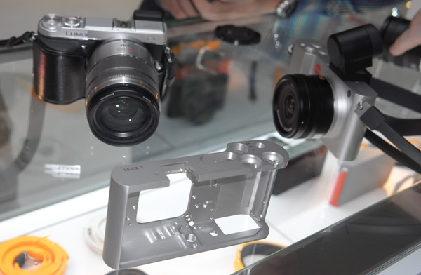 Note the size of the Leica T vs the Panasonic Lumix GX7. Also in the foreground, the precision-milled aluminium piece that holds every Leica T.