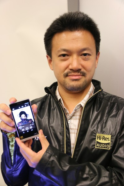 Tomoaki Sato holding up the Sony Walkman NWZ-ZX1.