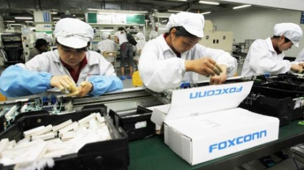 These assembly workers at Foxconn will soon be replaced with robots. </br> Image source: Ubergizmo
