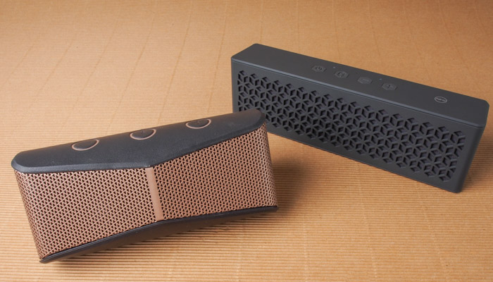 The wedge-shaped Logitech X300 and the more traditionally shaped Creative MuVo Mini.