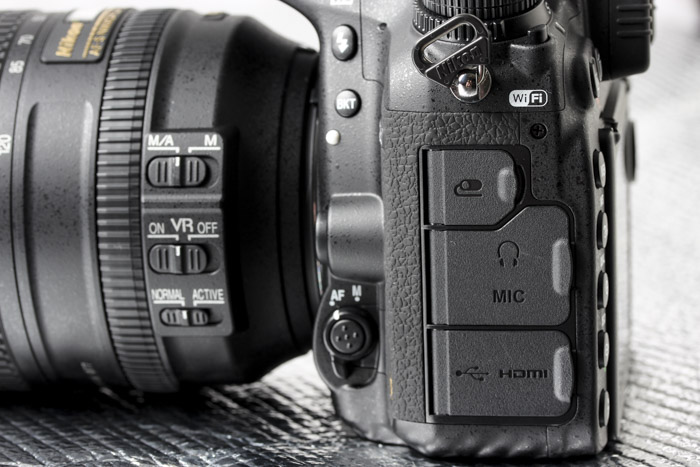 The bracketing button is now shifted to the front, while individual flaps for the remote and microphone/headphones for monitoring line the left side of the camera.