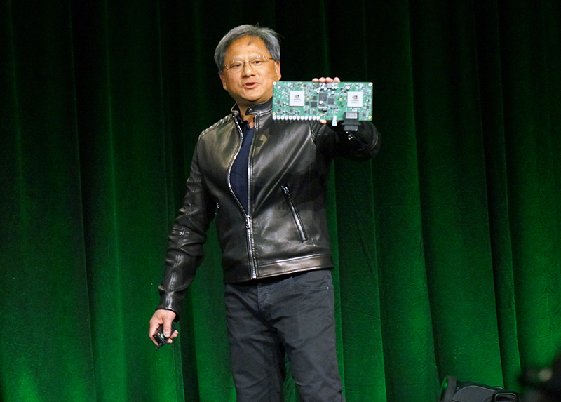 "NVIDIA CEO Jen-Hsun Huang holding up the Drive PX ""supercomputer for the car"", which has in excess of 2 teraflops of compute performance."