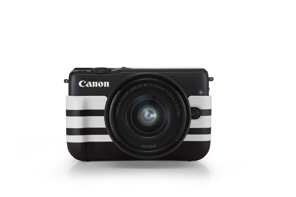 A black Canon EOS M10 with limited edition jacket in border pattern,