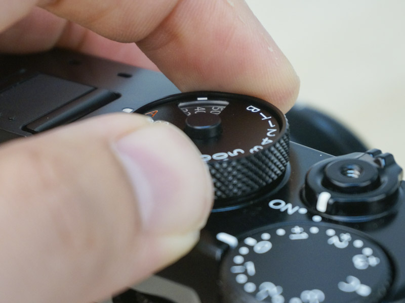 To adjust ISO, lift the sides of the shutter dial up and turn.