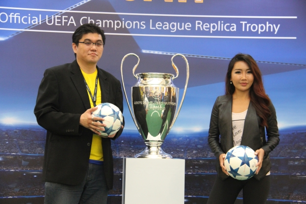 From L-R: Lawrence Lim, Business Manager, Sony Mobile Malaysia and Michelle Lee, host of Football Overload with the UEFA Champions League trophy replica between them during the event.