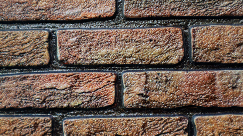 This is not an actual brick wall - this is a print by Canon, and it captures the textures and gloss as printable data before it goes out as a copy.