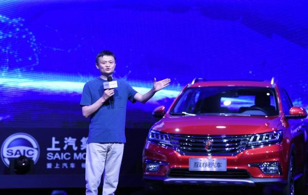 Jack Ma, CEO, Alibaba; with the Roewe RX5 that uses an infotainment system that can interact with other Internet connected devices. <br> Image Source: Forbes