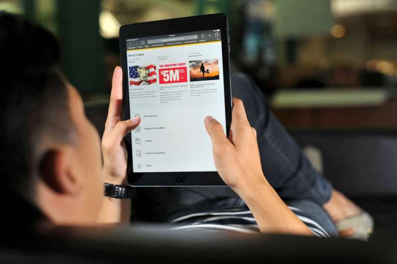 Posed photograph of a man looking at the Singapore Pools website on a tablet. Credit: ST FILE