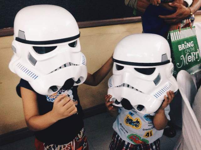 The children of the PGH pediatric ward trying on the Stormtrooper helmets.