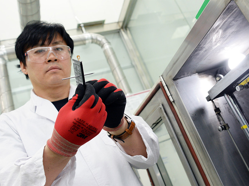 An LG technician holds up a battery that has been punctured by a nail. Image source: LG.