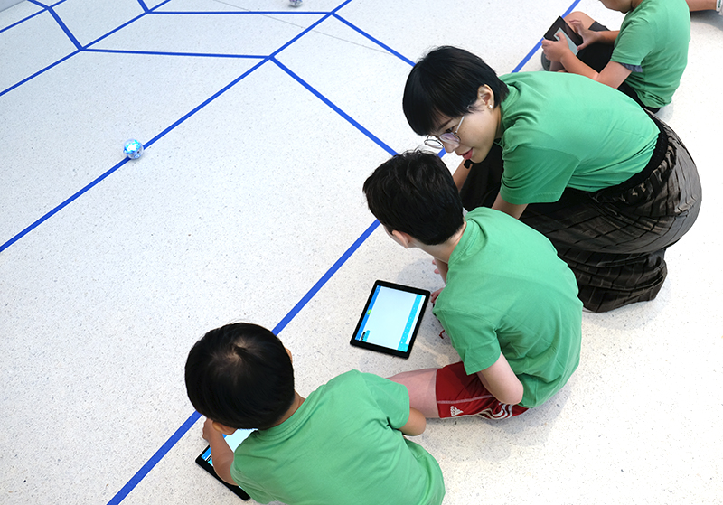 The first mission requires children to program their Sphero robots to roll to the first blue line in front of them.