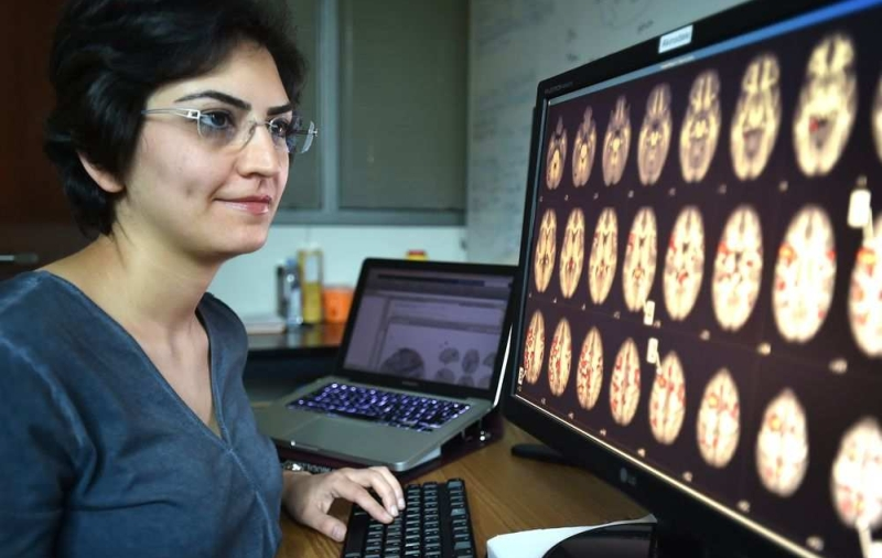 Mina Gheiratmand, primary author of the research study, looking at MRI scans that help identify schizophrenia patients. <br>Image source: Edmonton Journal.