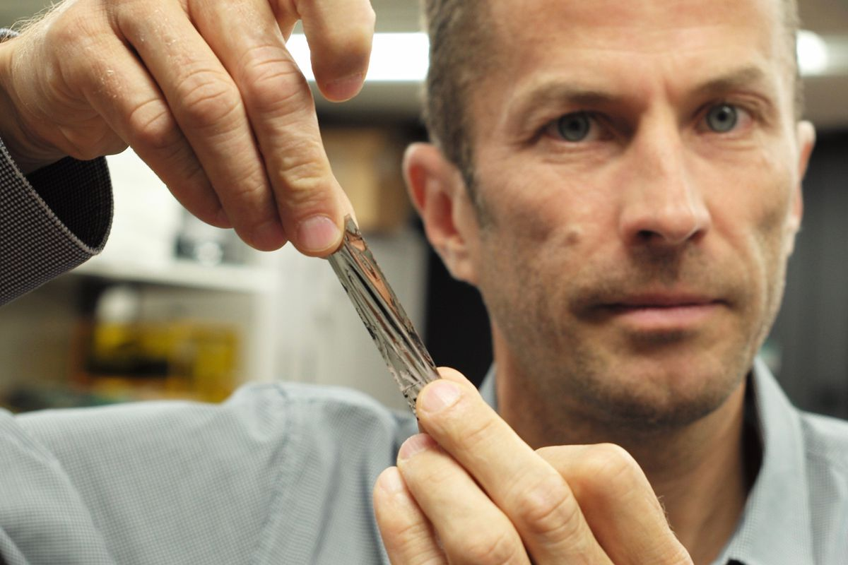IBM scientist Dr. Mark Lantz holds a one square inch piece of sputtered tape, which can hold 201 gigabits, a new world record. <br>Credit: IBM Research, The Verge.