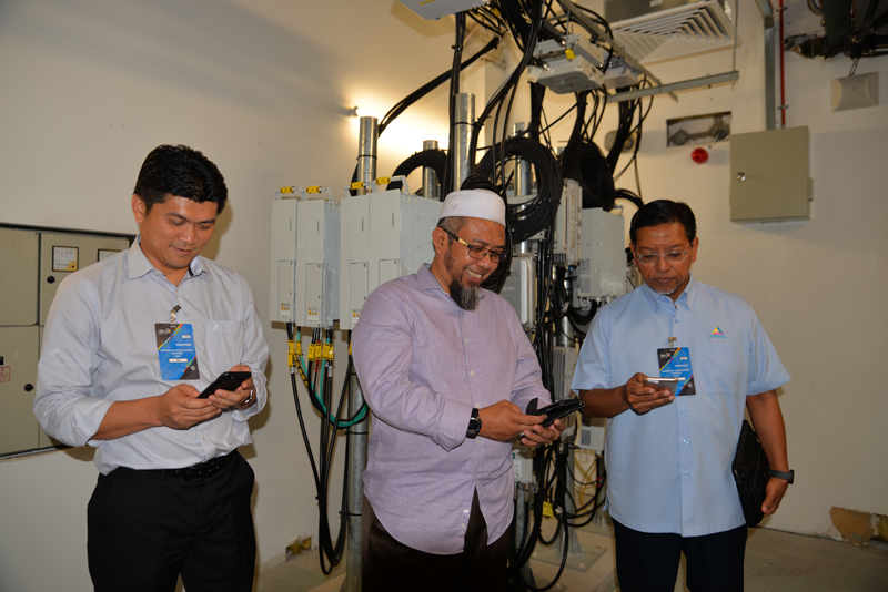 From L-R: Nor Azhar Hassan, Head of Infrastructure, Malaysian Communications and Multimedia Commission; Tn. Haji Abdurrahman Othman, Director of Corporate Affairs, edotco Malaysia; and Dato' Mohd Ali Hanafiah Mohd Yunus, Communications and Digital Ecosystem Sector Chief Officer, Malaysian Communications and Multimedia Commission, checking the connectivity on their mobile phones in the edotco hub room in the Axiata Arena in Bukit Jalil.