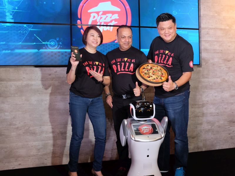 (From L-R) Jean Ler, Chief Marketing Officer, Pizza Hut Malaysia; Merrill Pereyra, Chief Executive Officer, QSR Brands (M) Holdings Bhd; Eric Leong, General Manager, Pizza Hut Malaysia; and Sally, one of two greeting robots at Pizza Hut's new digital concept store in Sunway Pyramid.