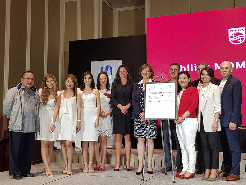 Philips executives, VIP guests, and MOM for Moms celebrity ambassadors pose for a photo after the ceremonial signing of the MOM for Moms shirt as a symbol of their support for the campaign.