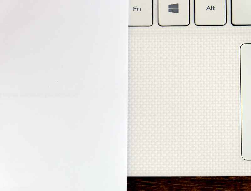 Here's a piece of paper juxtaposed with the 'alpine white woven glass fiber' palm rest of the XPS 13. I leave you to make your own conclusions.