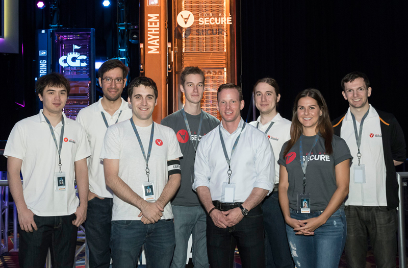 ForAllSecure engineers pose with their creation, Mayhem, at the closing ceremony in 2016. (Image source: DARPA via IEEE Spectrum)