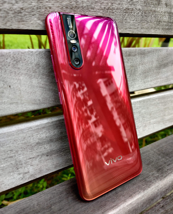 The back of the phone is very red. But sadly, it's plastic and not glass.