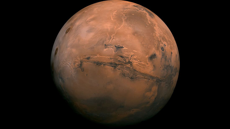 Valles Marineris is the largest canyon in the solar system, and you can see it here cutting across the face of Mars. It is over 3,000km long and up to 8km deep. (Image Source: NASA)