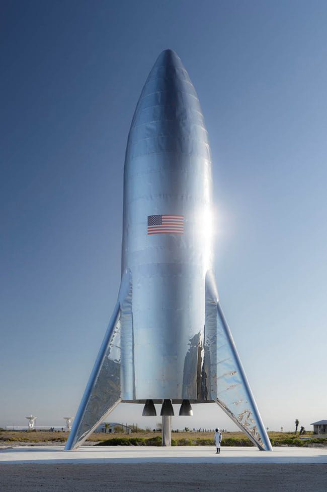 A gleaming Starship prototype stands at a SpaceX facility in Boca Chica Village, Texas.