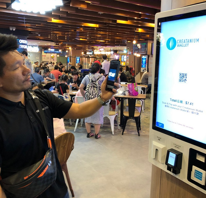 A staff demonstrating how visitors to the Kopitiam at Singapore's Funan mall can buy food and drinks using the Finney QR scanning function and pay via a cryptocurrency token called Creatanium.