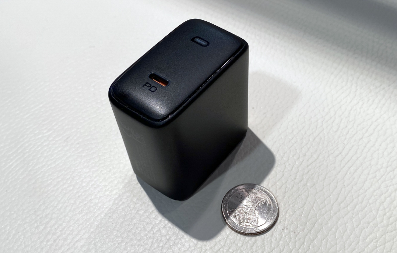 This is Aukey's 100W Omnia charger next to a US quarter.