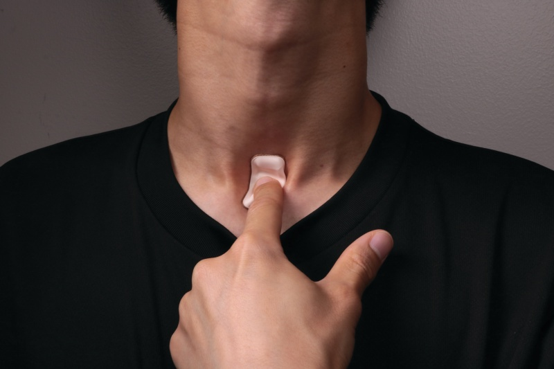 The wireless sensor can sit on the throat to monitor coughs, fever and respiratory activity to diagnose Covid-19. <br>Image source: Northwestern Now.