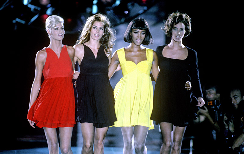 Linda Evangelista, Cindy Crawford, Naomi Campbell and Christy Turlington, pictured here at Gianni Versace's Fall 1991 show, will revisit their iconic modeling careers in 'The Supermodels'. (Image: Apple.)