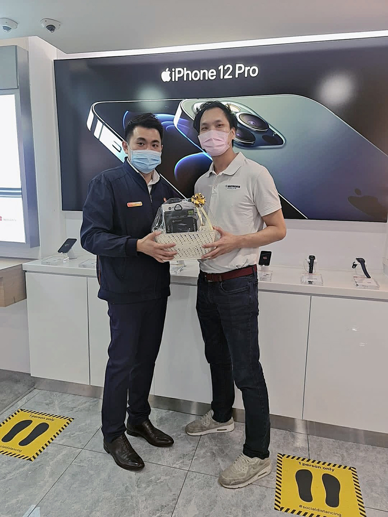 Mr Seo Jialiang, Jerald (right), lucky winner of the hamper with his purchased iPhone 12 mini. Image credit: M1.