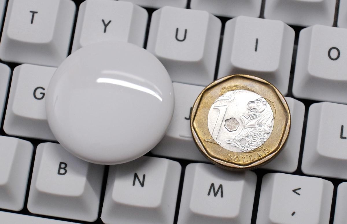 An AirTag next to a dollar coin.
