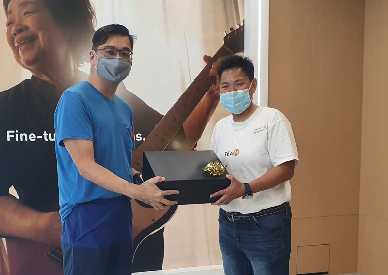 M1's very first iPhone 13 customer swings by, snags and bonus hamper for his efforts. Image credit: M1.