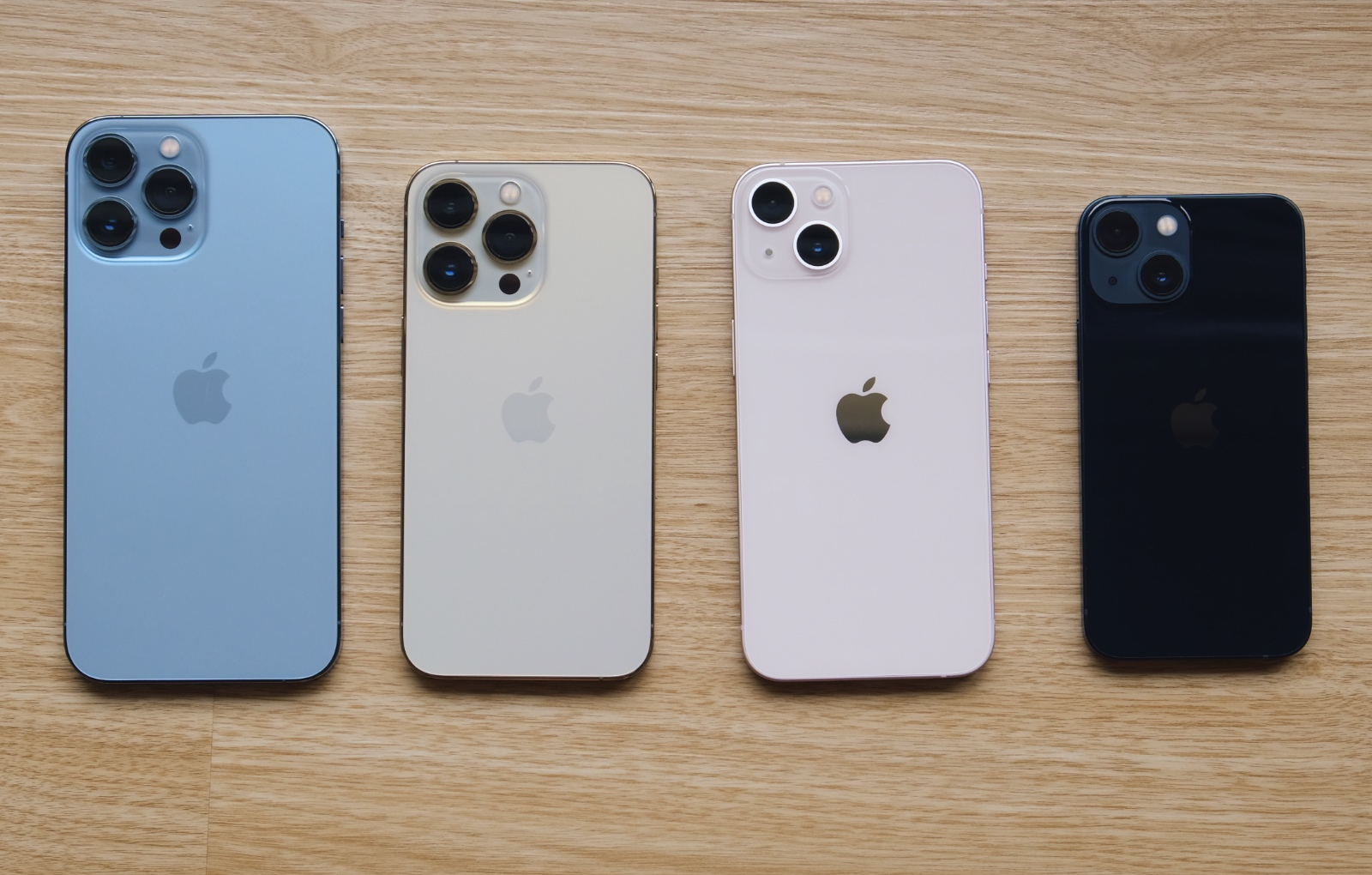 From left to right: iPhone 13 Pro Max in Sierra Blue, iPhone 13 Pro in Gold, iPhone 13 in Pink, and iPhone 13 Mini in Midnight.