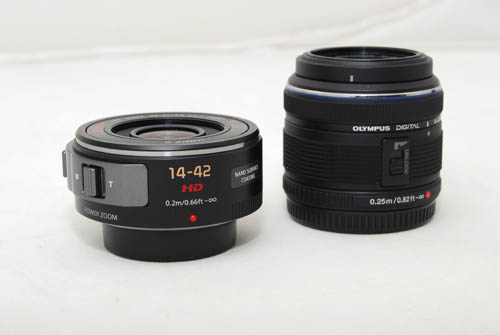 The X 14-42mm lens in comparison to a standard 14-42mm (an Olympus shown here). Both cameras have their lens protectors on below and the Olympus lens is locked.
